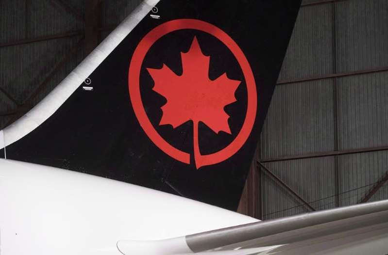 a black sign with white text: The Air Canada is seen on an aircraft at a hangar at Toronto Pearson International Airport in Mississauga, Ont., February 9, 2017. Air Canada is cancelling all flights to Italy starting Wednesday, following the lead of European carriers that have halted service to a country now under nationwide lockdown to contain the new coronavirus. THE CANADIAN PRESS/Mark Blinch