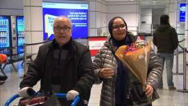 a person holding a bag of luggage: Mohammed El Aidi was waiting with flowers when his wife, Ouafae, arrived at Trudeau Airport.