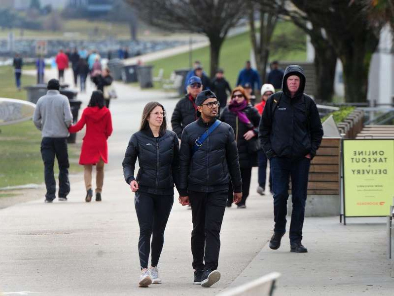 a group of people walking down the street: Walkers and runners along English Bay as health officials have recommended strict social distancing to prevent the spread of COVID-19 in Metro Vancouver.