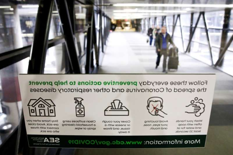 FILE PHOTO: A sign featuring preventative actions to stop the spread of Coronavirus is pictured at Seattle-Tacoma International Airport as passengers exit the main terminal, in SeaTac, Washington