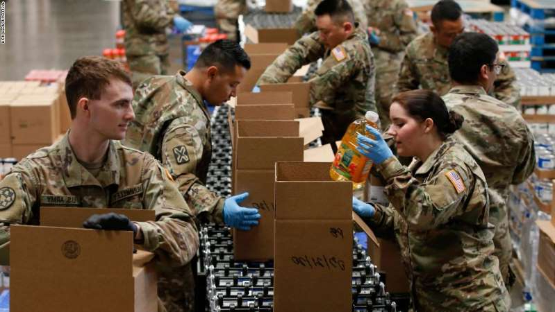 a group of people looking at a laptop: Members of 115th Regional Support Group of the California National Guard load boxes with food at the Sacramento Food Bank and Family Services in Sacramento, Calif., Saturday, March 21, 2020. Food banks have been hit hard by a shortage of volunteers due to the mandatory stay-at-home order caused by the coronavirus.