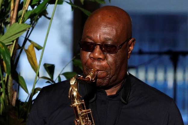FILE - In this Jan.24, 2018 file photo, saxophonist Manu Dibango performs during Franck Sorbier's Haute Couture Spring-Summer 2018 fashion collection in Paris. Renowned jazz man Manu Dibango, to many the beloved