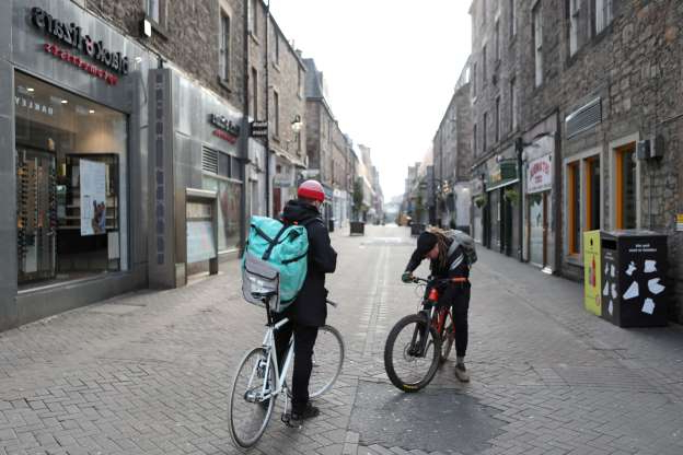 Slide 1 of 50: Two delivery boys on bicycles are seen, as the spread of the coronavirus disease (COVID-19) continues in Edinburgh, Scotland, Britain, March 24, 2020.