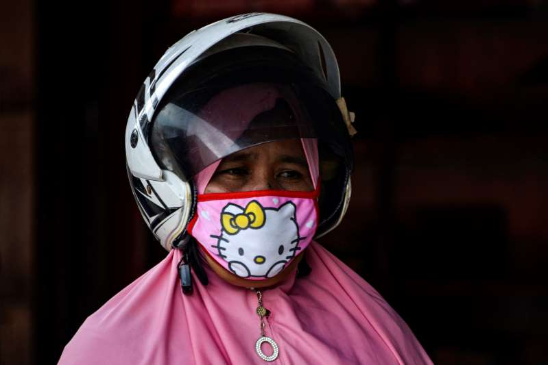 a close up of a person wearing a helmet: A women wears a face mask, amid concerns of the COVID-19 coronavirus, at a street market in Banda Aceh on March 25, 2020. (Photo by CHAIDEER MAHYUDDIN / AFP) (Photo by CHAIDEER MAHYUDDIN/AFP via Getty Images)