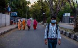 A man with a protective mask walks on a deserted road, amid a nationwide lockdown over highly contagious novel coronavirus on Tuesday in New Delhi.