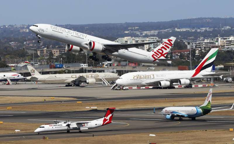 a airplane that is sitting on a runway at an airport:  Virgin Australia has stood down 8000 workers and slashed domestic flights amid the coronavirus fallout. (AAP Image/Daniel Munoz) NO ARCHIVING