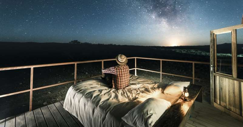 a bed with a wooden fence: While physical travel isn't advised, mental travel is highly recommended.