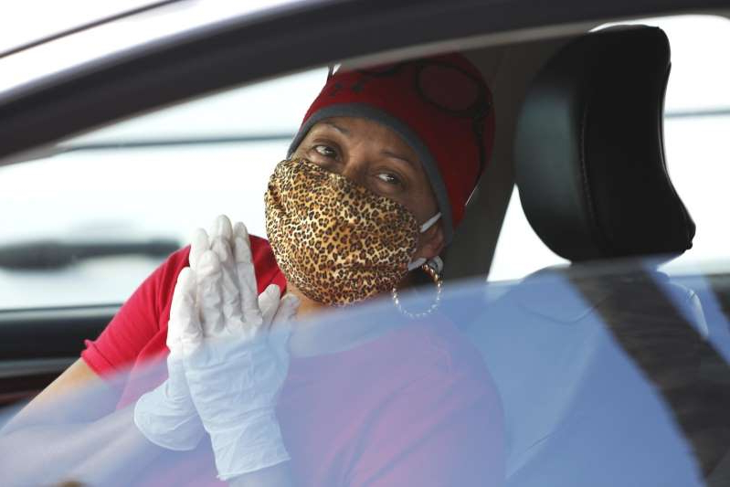 a close up of a car window: LOS ANGELES, CA - MARCH 25, 2020 - Dede Oneal puts together prayerful hands while waiting in a line of cars to receive a test for COVID-19 at the Crenshaw Christian Center at 7901 S. Vermont Avenue in South Los Angeles on March 25, 2020. Attention Editor: Oneal is spelled this way.