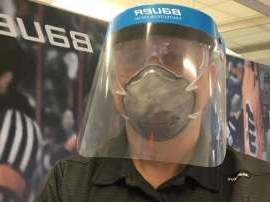 a close up of a man with a helmet on: People using the Bauer shield must still have a mask to cover their nose and mouth.