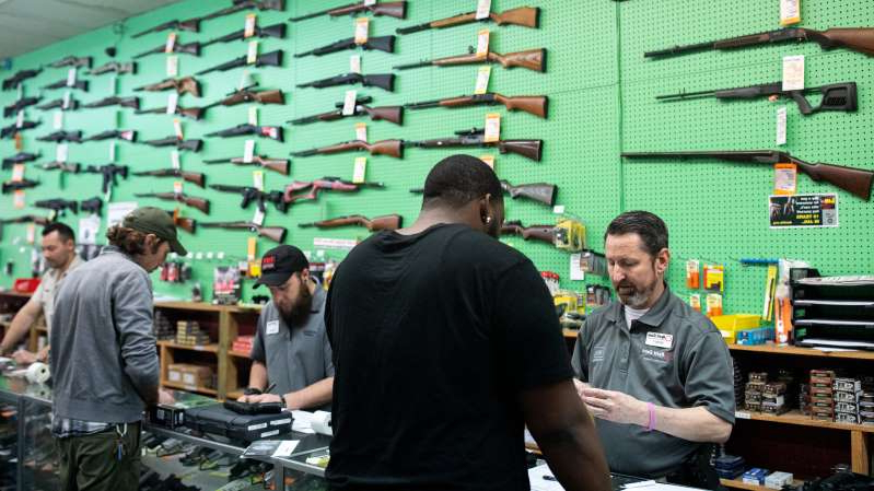 a group of people standing in front of a computer: A gun shop in Charlotte, N.C., where the owner says sales of firearms have soared in recent weeks.