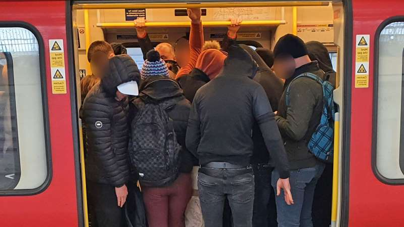 a group of people waiting to board a bus: A packed train in London on Monday, when an Italian expert says the UK should have been locked down