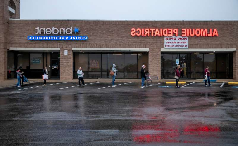 a group of people walking in front of a building: People wait in line with appropriate social distancing for the 8 a.m. opening of the H-E-B in the Tanglewood Village Shopping Center in South Austin, Texas on Sunday March 22, 2020, amid the coronavirus pandemic.