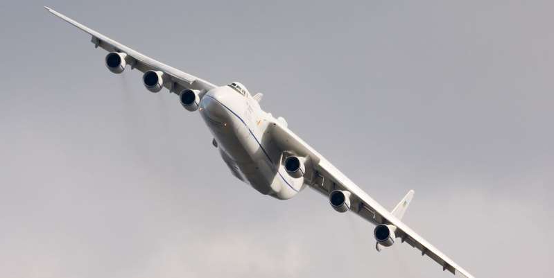 a large passenger jet flying through a cloudy blue sky: Aviation enthusiasts, rejoice: After a long overhaul, Antonov's big bird, the AN-225, has finally returned. Learn more about the largest plane in the world.