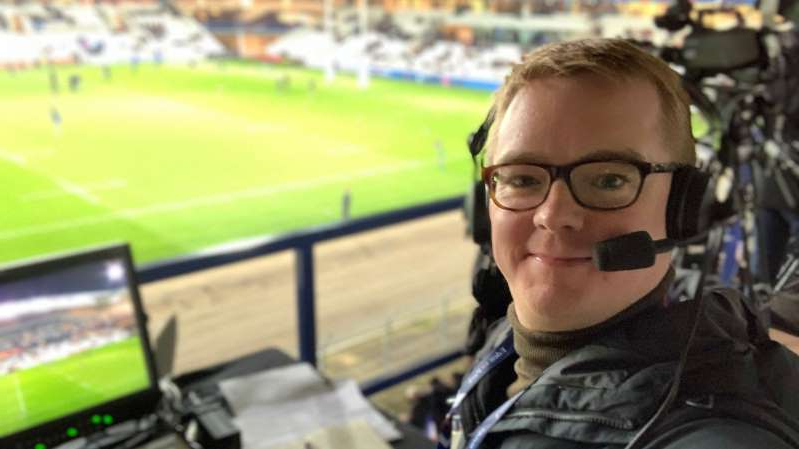 a man wearing glasses: Nick Heath, a rugby announcer, has been chronicling his London neighborhood with videos that have become popular on social media.