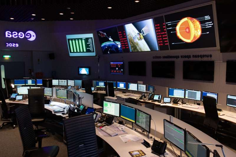 a screen shot of a computer desk in front of a store: A picture taken on February 7, 2020, shows the main control room of the European Space Operations Centre (ESOC) of the European Space Agency (ESA) in Darmstadt, western Germany.