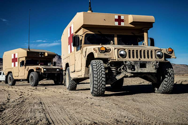 a truck driving down a dirt road: Field litter ambulances arrive with simulated patients during a mass casualty scenario at the field hospital at Sierra Army Depot in California during the United States Forces Command Medical Emergency Deployment Readiness Exercise on Oct. 28, 2019. The realistic event gave soldiers a chance to test their skills and knowledge in the event of a real mass casualty incident. (U.S. Army Forces Command)