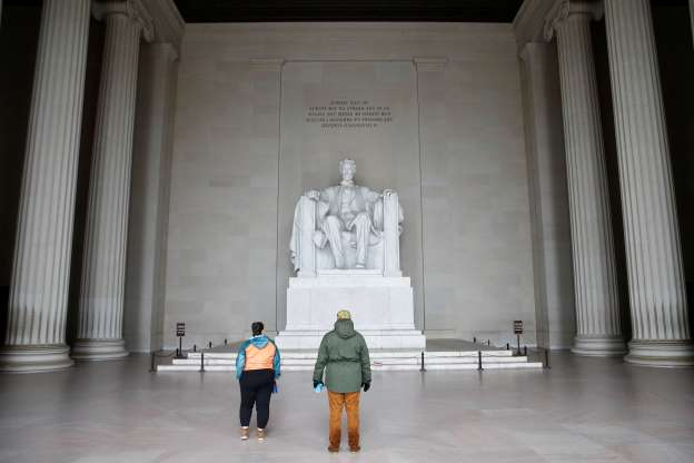 Slide 1 of 50: Dylan Kyriacopoulos, left, and his fiance Mary Williams visit an empty Lincoln Memorial in Washington, Wednesday, March 25, 2020. Officials have urged Washington residents to stay home to contain the spread of the coronavirus.
