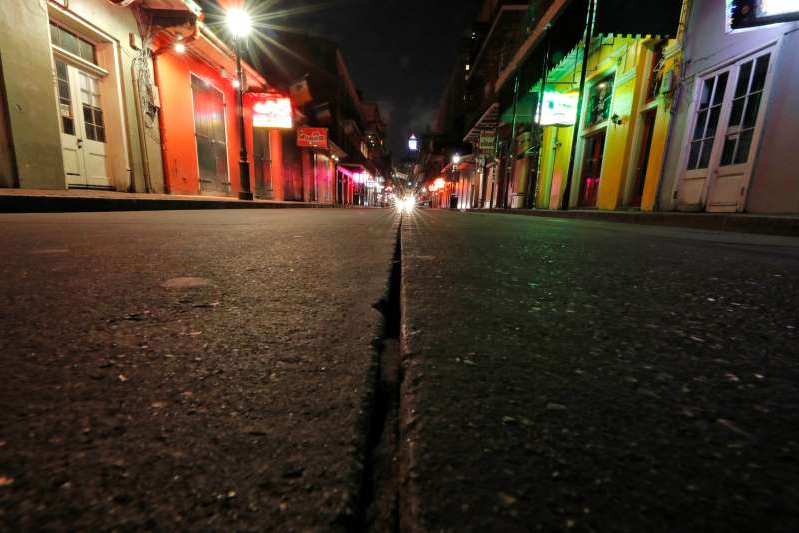 a city street at night: In this Thursday, March 19, 2020, file photo, a view of the nearly deserted scene on Bourbon Street, which is normally bustling with tourists and revelers, in the French Quarter of New Orleans. Like many cities around the country, New Orleans is currently under a shelter-in-place order as it grapples with a growing number of coronavirus cases.