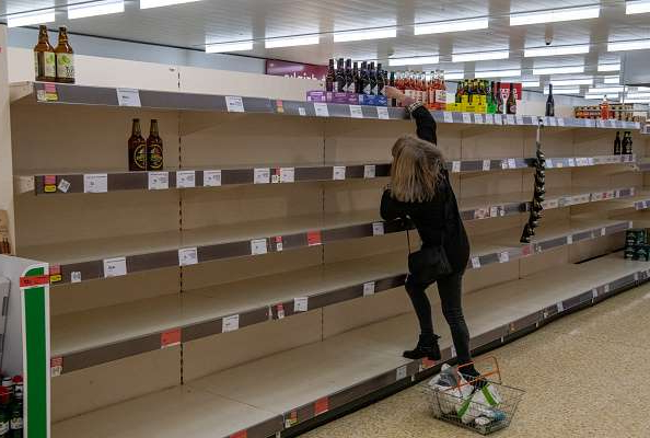 CHIPPENHAM, ENGLAND - MARCH 25: A woman reaches for bottles of cider amongst emptied shelves at a Sainsburys supermarket as the outbreak of coronavirus intensifies on March 25, 2020 in Chippenham, United Kingdom. The United Kingdom has seen mass panic buying in food stores since British Prime Minister, Boris Johnson, announced strict lockdown measures urging people to stay at home with many items now being rationed by supermarkets and social distancing measures being put in place. The Coronavirus (COVID-19) pandemic has spread to at least 182 countries, claiming over 18,000 lives and infecting hundreds of thousands more. (Photo by Chris J Ratcliffe/Getty Images)