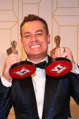 Grant Denyer holding a pair of people posing for the camera: 'It feels wrong and self-indulgent in these times': Grant Denyer has called for this year's Logie Awards to be postponed due to the coronavirus pandemic. Pictured on July 1, 2018