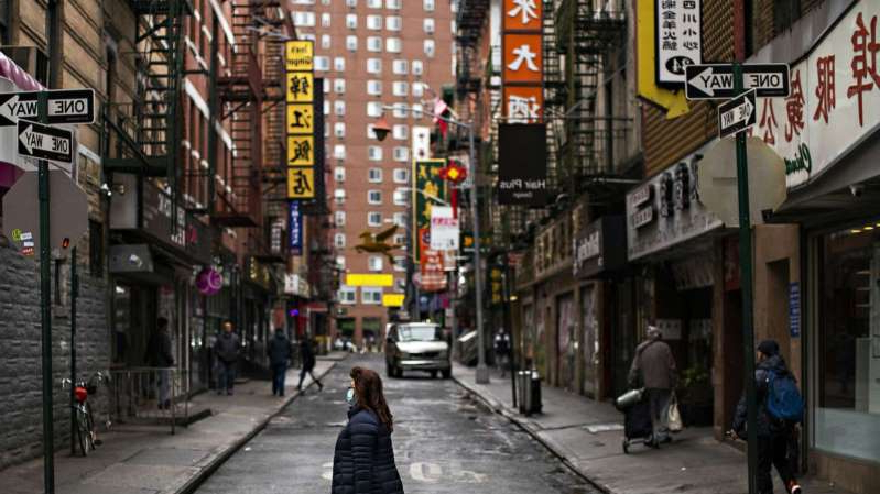 a person walking down a city street: A woman walks in the Chinatown area of Manhattan during the coronavirus outbreak, in New York City, March 17, 2020.