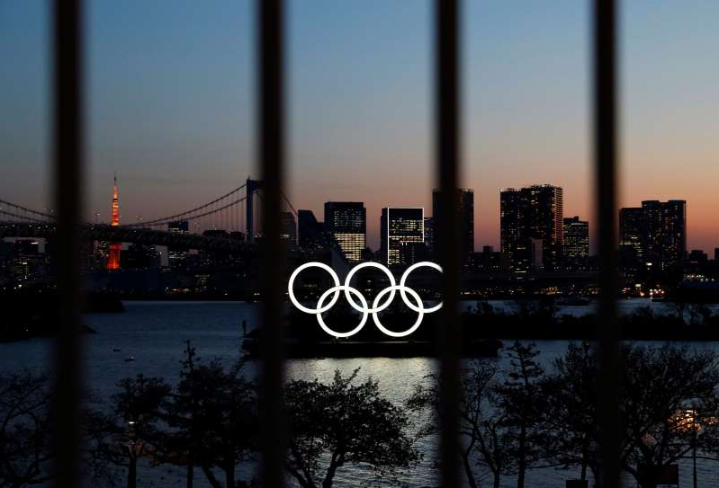 a bridge over a body of water: The Olympic rings are pictured at dusk through a steel fence, at the waterfront area of the Odaiba Marine Park, after the postponing of the Olympic Games Tokyo 2020, due to the outbreak of coronavirus disease (COVID 19), in Tokyo