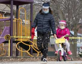 a group of people riding on the back of a bicycle: A woman and child wearing masks and full face shields pass a taped off play structure in Toronto on Thursday March 26, 2020.