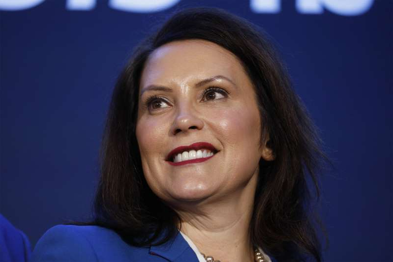 a close up of Gretchen Whitmer in a blue shirt: Michigan Gov. Gretchen Whitmer stands on stage at an event where General Motors announced that GM's Detroit-Hamtramck Assembly plant will build the all-electric Cruise Origin self-driving shuttle on Jan. 27, 2020 in Hamtramck, Mich.
