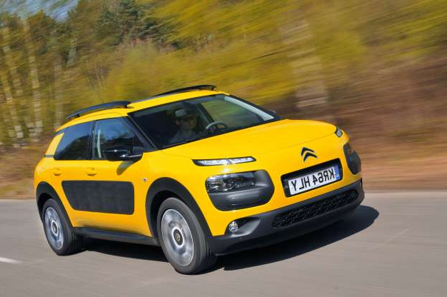 a yellow and black car driving on a road: Citroën C4 Cactus: there's no funkier way to enter a ULEZ zone