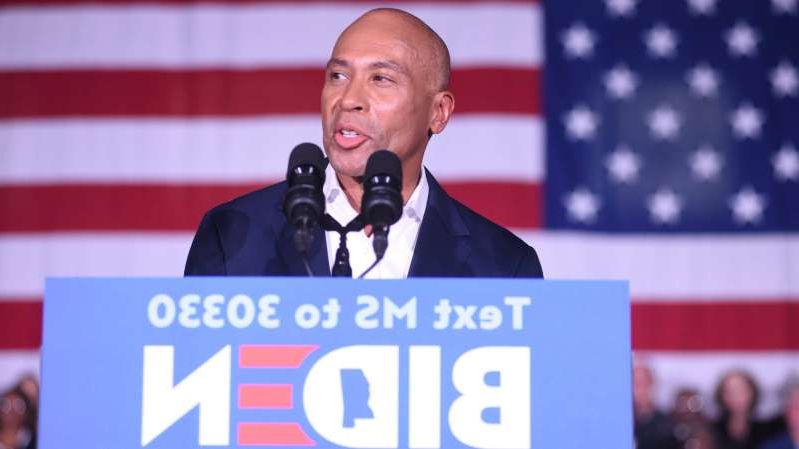 Deval Patrick holding a sign in front of a crowd: Deval Patrick, the former governor of Massachusetts, is now a co-chair of a partnership of Democratic groups supporting Joseph R. Biden Jr.