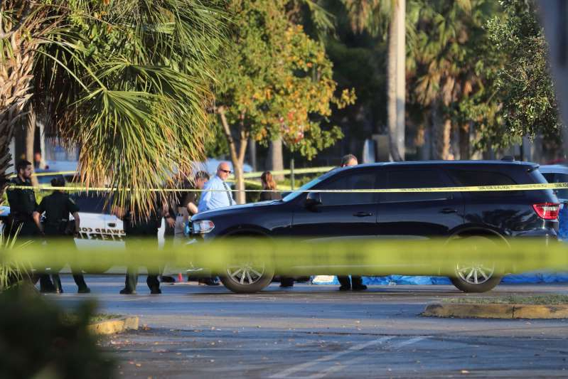 a car parked on the side of a road: A man and woman were fatally shot in a Lauderdale Lakes shopping center parking lot that was crowded with people despite Broward County's COVID-19 isolation rules, the Broward Sheriff's Office said.
