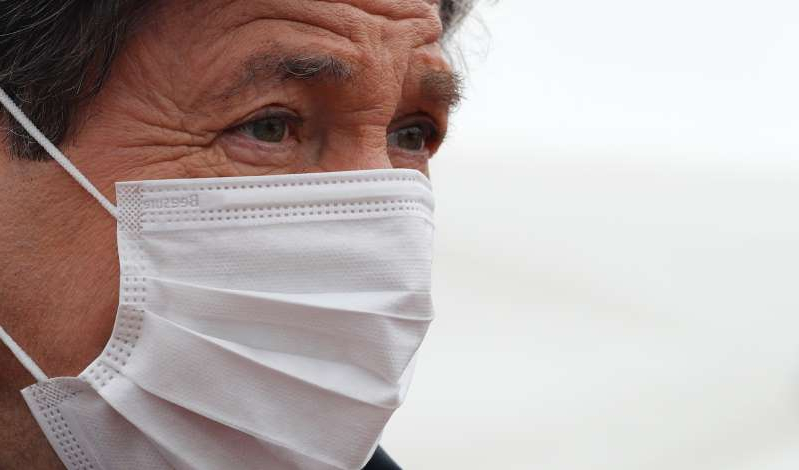 a close up of a person wearing a mask: Christian Estrosi , mayor of Nice stands in front of temporary