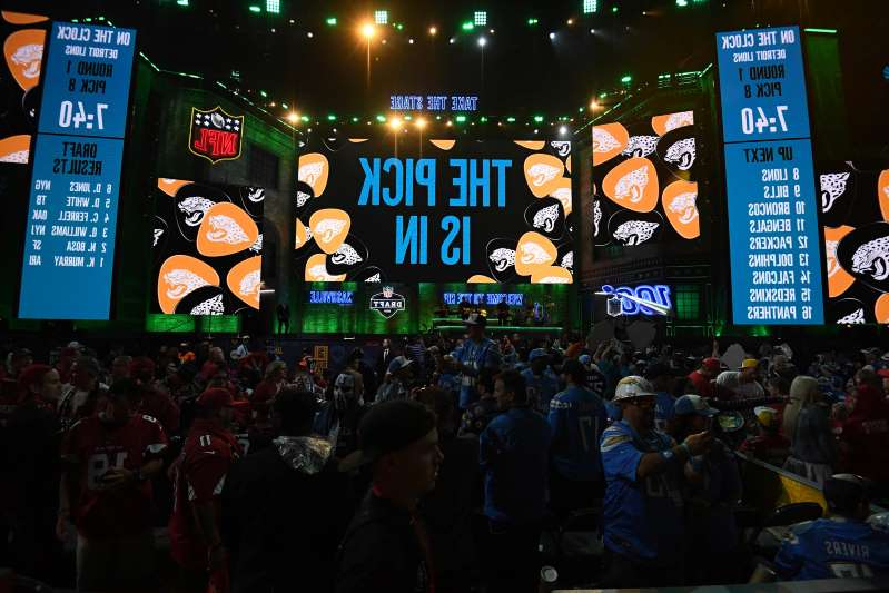 a group of people performing on stage in front of a store: The NFL is making some accommodations amid a completely overhauled draft.