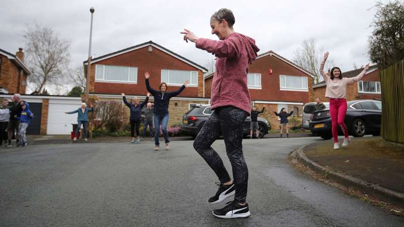 a man flying through the air while riding a skateboard in a parking lot: Janet Woodcock leads a dance class for residents in a street in Frodsham