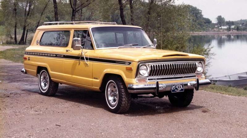 a yellow and black truck parked in front of a car: 1975 Jeep Cherokee Chief
