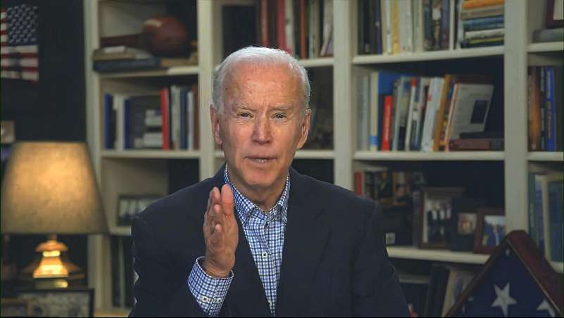 Joe Biden holding a book shelf: In this image from video, former vice president Joe Biden speaks during a virtual press briefing on March 25.