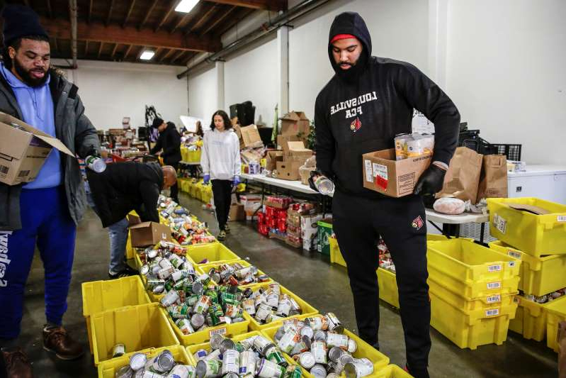 a person preparing food in a box: Jared Goldwire, of Tacoma, a defensive end on the University of Louisville football team, and Robert Christopher III of Seattle, organize food donations at the Emergency Feeding Program of Seattle and King County to hand out at a drive-through pick up amid the coronavirus outbreak, in Renton, Washington, March 16, 2020. REUTERS/Jason Redmond