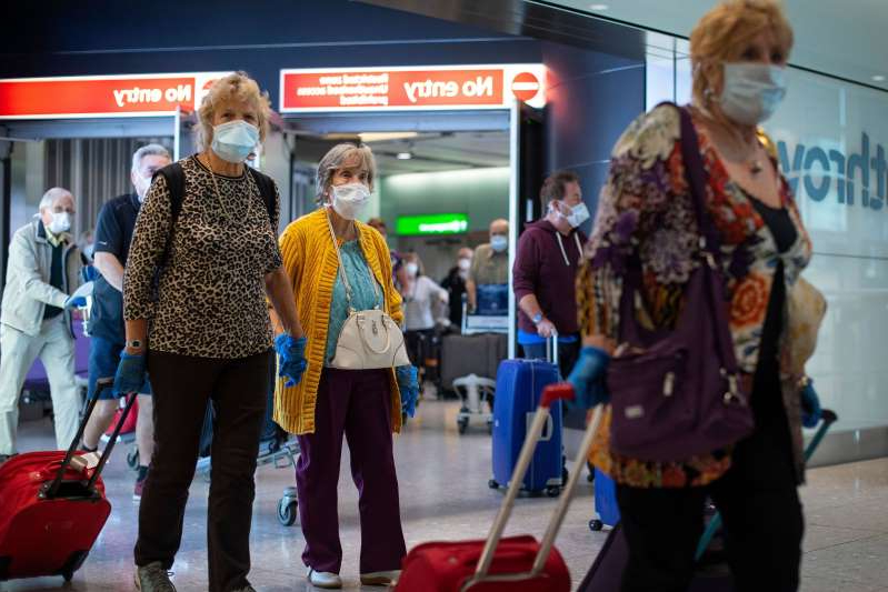a group of people wearing costumes: Passengers from the Holland America Line ship Zaandam walk through arrivals in Terminal 2 at Heathrow Airport in London, after flying back on a repatriation flight from Florida. (Photo by Victoria Jones/PA Images via Getty Images)