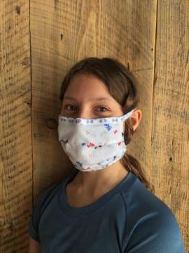 a little boy looking at the camera: Pikssii Crowshoe, 11, models a mask sewn by the women of the Pincher Creek Hutterite Colony. A group of volunteers at the colony is sewing masks to distribute to Indigenous communities and health-care workers in southern Alberta.