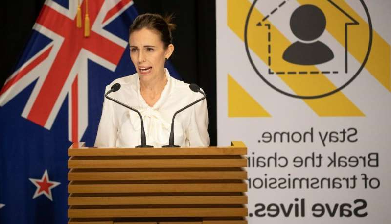 Jacinda Ardern holding a sign: Watch Jacinda Ardern and the Ministry of Health's Sunday COVID-19 press conference.