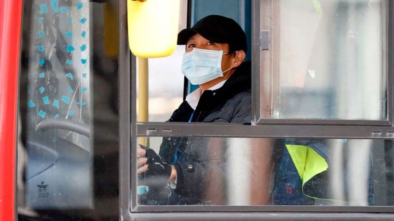 a person sitting in front of a window: A new trial of how passengers board buses is being launched to protect drivers from contracting coronavirus