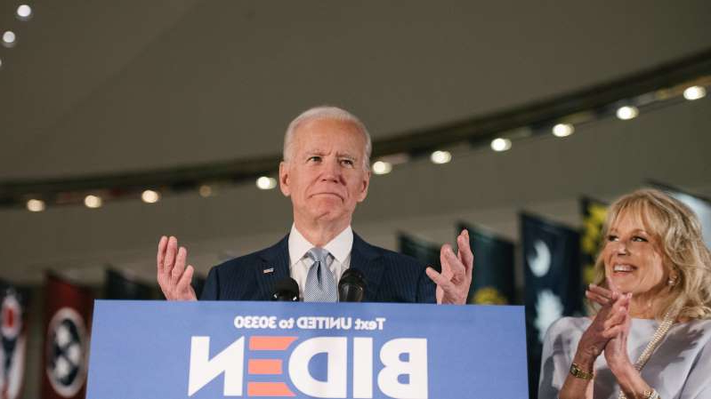 Joe Biden holding a sign posing for the camera: Former Vice President Joseph R. Biden Jr., with his wife, Jill Biden, is now the standard-bearer of the Democratic Party.