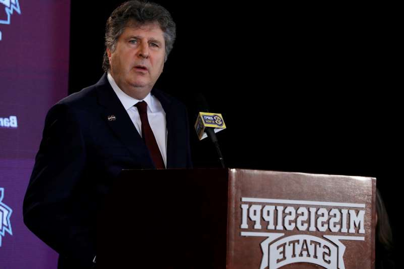 Mike Leach wearing a suit and tie and holding a sign: Mississippi State coach Mike Leach apologizes for tweet