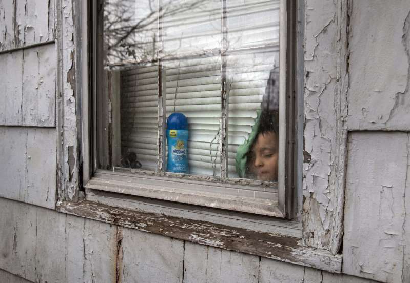 a person standing in front of a window: A 4-year-old undocumented Honduran immigrant, sick and isolated with his family for two weeks, looks outside a bedroom window in Mineola, N.Y., on March 30. (John Moore/AFP/Getty Images)