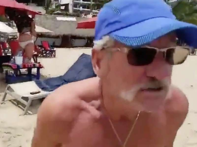 a person wearing a blue hat: A tourist confronts a journalist reporting live from a Puerto Vallarta beach in a screenshot from a video.