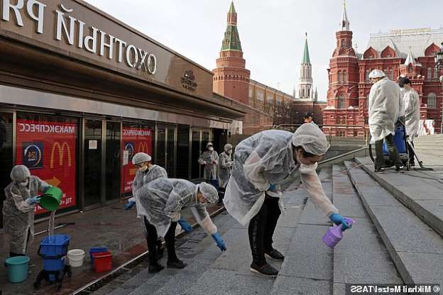 a group of people walking in front of a building: Sanitary workers in face masks clean up and disinfect steps outside a Moscow shopping centre. Infections today jumped by 1,786 to 11,917, marking the biggest daily rise in the country's accelerating outbreak