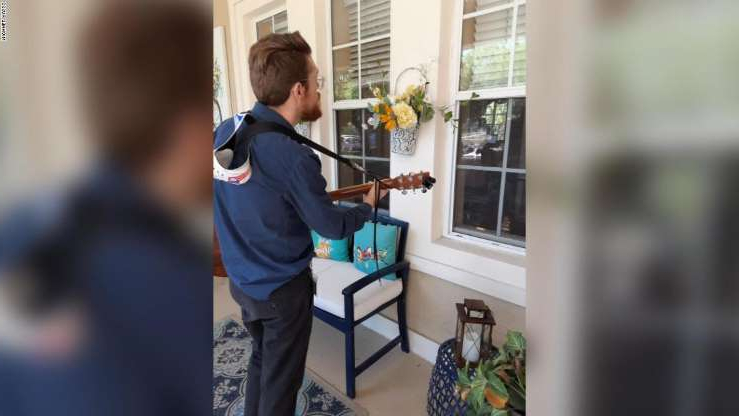 a young boy standing in front of a window: Hospice worker Michael Russo still sings to his patients any way he can reach them.