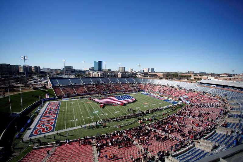 FILE- This Dec. 30, 2019, file photo shows many empty seats as a flag is displayed on the field before the NCAA First Responder Bowl college football game between Western Michigan and Western Kentucky in Dallas. Bowls outside the College Football Playoff structure might excite only the most ardent fans of the participating teams, be played in half-empty stadiums and prompt howls about there being too many games. They aren't going away, though. There'll be three more next season, bringing the total number of bowls to 42. (AP Photo/Roger Steinman, File)