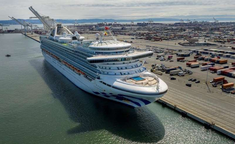 a boat is docked in a harbor: The Grand Princess docks at the Port of Oakland in Oakland, Calif., on Monday, March 9, 2020.