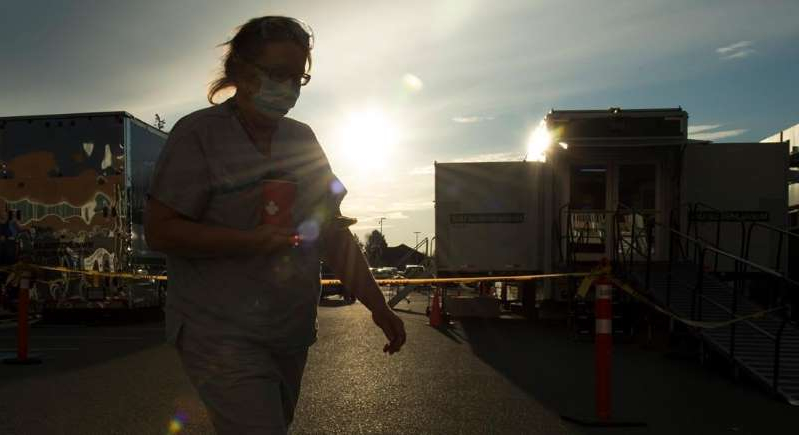a man standing in a room: A health-care worker is silhouetted as they walk past the British Columbia mobile medical unit set up outside of Abbotsford Regional Hospital in Abbotsford, B.C. Tuesday, April 14, 2020. The mobile medical unit was deployed to Abbotsford to assist with the COVID-19 outbreak that has occurred at the Mission Correctional Institution.
